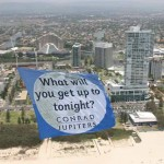 ABC Heli towing Conrad Jupiters banner past beachfront apartments