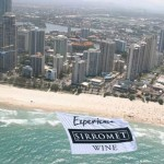 ABC Heli towing Sirromet Wine banner past hundreds of beach-goers, and beachfront apartment windows